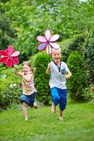 Kinder laufen mit Windrad im Garten