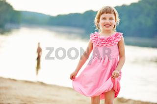 Mädchen im rosa Kleid am See