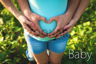 Man's hands embrace a belly of the pregnant woman