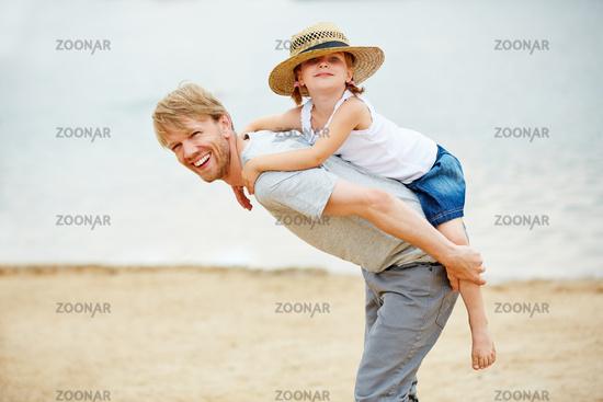 Lachender Vater trägt Tochter huckepack