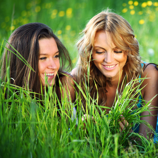 girlfriends lays on green grass and smile