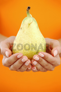 pear in woman hands close up