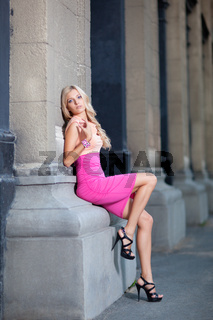 beautiful lady leans against columns in a dress.