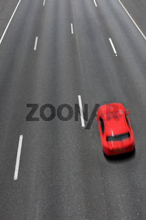 Red car moves fast on highway.