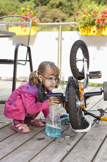 Little girl cleans her bike