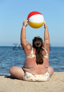 overweight woman doing gymnastics on beach