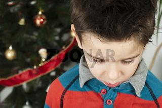 Unhappy little boy on christmass