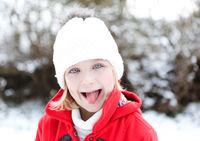 Kind im Winter streckt Zunge raus