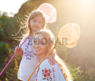 Cheerful mother and her daughter playing in a field with insect net