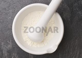 Weißes Pulver in einem Mörser mit Pistill