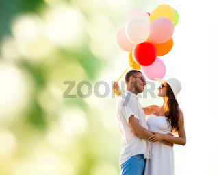 smiling couple with air balloons outdoors