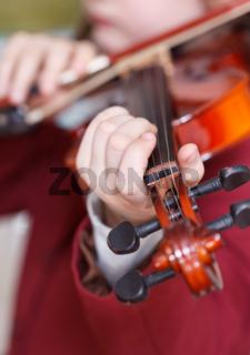 girl plays on violin - chord on fingerboard