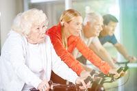 Alte Frau beim Spinning im Fitnesscenter