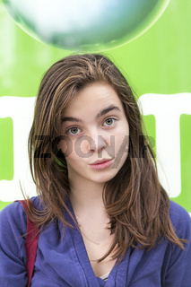 portrait of a female smirking teenager with a big drop in background