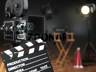 Video, movie, cinema concept. Retro camera, flash, clapperboard and director's chair in dark studio with dof effect.