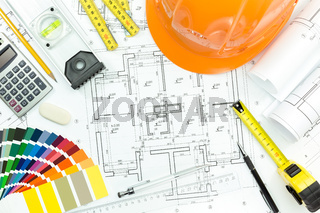 Engineer workplace with helmet, blueprint, and measuring tools