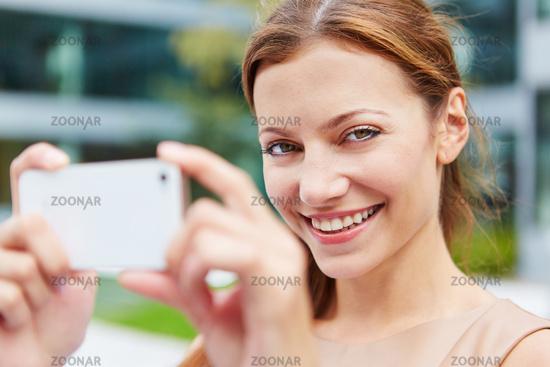 Lächelnde Frau fotografiert mit ihrem Smartphone