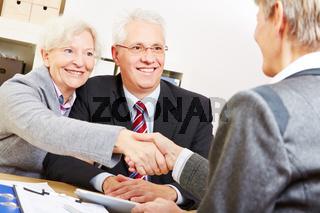 Paar Senioren schüttelt Hände mit Berater