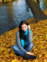 Woman in Autumn Outfit Sitting on Dry Leaves