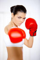 Determined woman wearing red boxing gloves