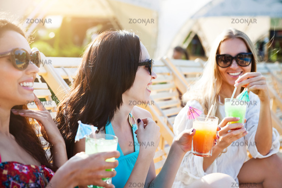 Happy girls with beverages on summer party