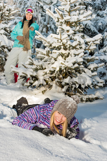 Two female friends enjoy snow winter countryside