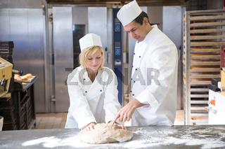 Baker instruction apprentice in kneading bread dough