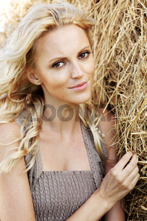 portrait of a girl next to haystack close