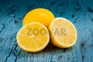 Lemon and cut half slice on blue wooden background