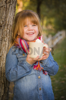 Cute Young Girl Holding Cocoa Mug with Marsh Mallows Outside