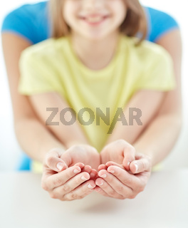 close up of woman and girl with cupped hands