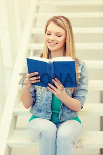 smiling teenage girl reading book