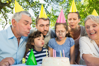 Extended family blowing cake outdoors