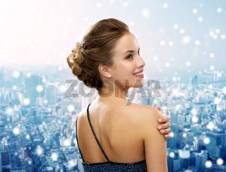 smiling woman in evening dress wearing earrings