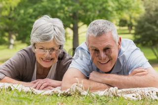 Portrait of senior couple lying at park
