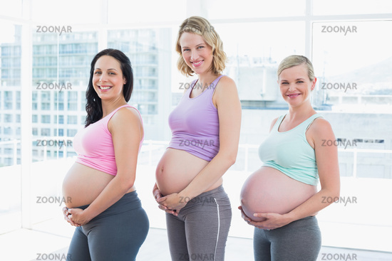 Happy pregnant women standing in a row