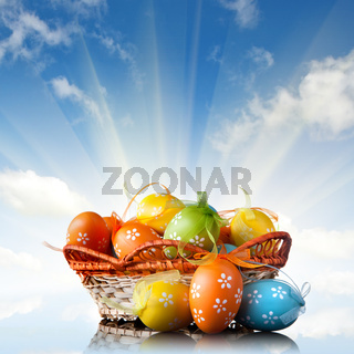 color easter eggs in basket against blue sky and clouds