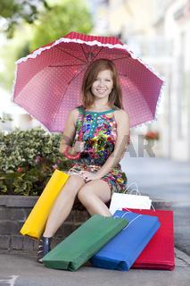 Junge Frau mit Schirm und Einkaufstueten