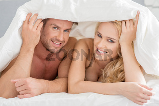 Young couple peeking out from under the bedclothes