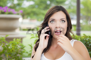 Stunned Young Adult Female Talking on Cell Phone Outdoors