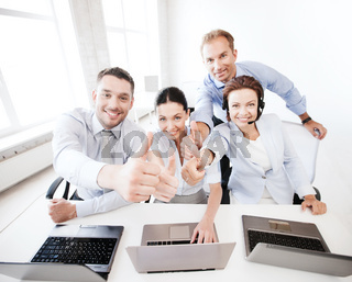 group of office workers showing thumbs up