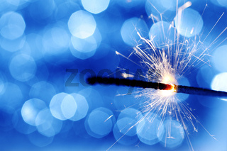 sparkler on blue bokeh background macro close up