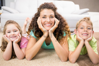 Happy siblings lying on the rug posing with their mother