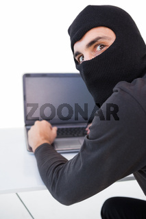 Burglar hacking into laptop while looking at camera