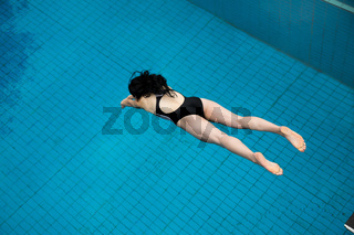 Girl jumps from a diving board at swimming pool