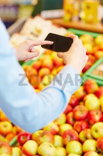 Hand scannt Informationen mit Smartphone im Supermarkt