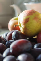 Plums and apples - autumnal fruits on the kitchen table