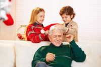 Kinder spielen mit Großvater an Weihnachten