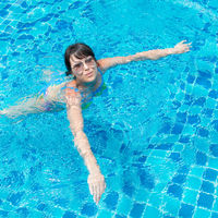 Beautiful young girl in sunglasses floating in the pool