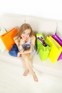 Stylish Girl with shopping bags on sofa